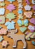 Les biscuits faits maison de pain d'épice avec le glaçage ont coloré des dessins sur le bois Image stock