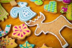 Les biscuits faits maison de pain d'épice avec le glaçage ont coloré des dessins sur le bois Photo libre de droits