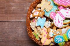 Les biscuits faits maison de pain d'épice avec le glaçage ont coloré des dessins sur le bois Image libre de droits