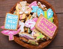 Les biscuits faits maison de pain d'épice avec le glaçage ont coloré des dessins sur le bois Photo stock
