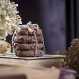Les biscuits foncés de chocolat avec des écrous sur le fond en bois foncé Images stock