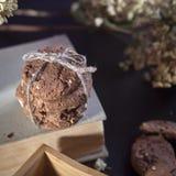 Les biscuits foncés de chocolat avec des écrous sur le fond en bois foncé Image libre de droits