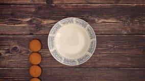 Les biscuits viennent dans le plat blanc sur le fond en bois - arrêtez le mouvement banque de vidéos