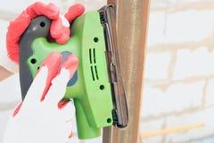 Les blocs de ponçage, machine de ponçage, remettent à travailleur dans les gants protecteurs spéciaux image libre de droits