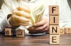 Les blocs en bois avec l'amende de mot et l'homme calcule le montant de l'amende Le concept de la punition financi?re P?nalit? co images libres de droits