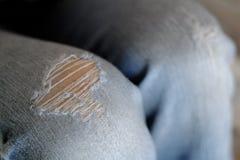 Les blues-jean façonnent avec des trous dans les genoux portés  photo stock