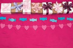 Les boîte-cadeau attachés avec le satin ont coloré le ruban sur un fond rose photographie stock