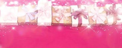 Les boîte-cadeau de bannière attachés avec le satin ont coloré le ruban sur un fond rose Images stock