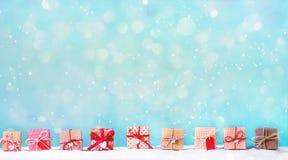 Les boîte-cadeau de Noël dans une neige ont couvert le paysage photographie stock