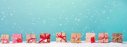 Les boîte-cadeau de Noël dans une neige ont couvert le paysage photo libre de droits