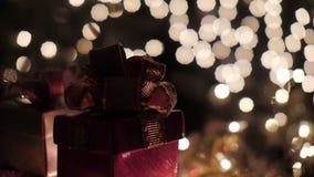Les boîte-cadeau rouges de Noël avec le bokeh de lueur allume le fond clips vidéos