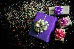 Les boîte-cadeau sur un fond de fête noir avec des étincelles Photos stock