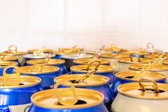 Les boîtes d'orangeade bleue et sur un fond carrelé, avec les séjour-sur-étiquettes se sont ouvertes Fait à partir de l'aluminium images stock