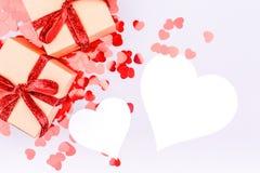 Les boîtes de métier avec le ruban rouge cintrent et scintillent des confettis de coeur vallée Photographie stock