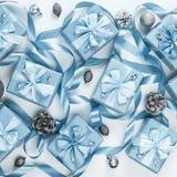 Les boîtes de Noël avec la couleur bleue de cadeaux sur la vue supérieure de fond de cônes de décor blanc d'écrous étendent à pla photos stock