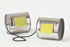 Les boîtes en fer blanc téléphonent avec la note de papier - concept de communication Images libres de droits