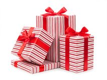 Les boîtes rayées avec des cadeaux ont attaché des arcs sur le fond blanc photos libres de droits
