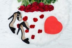 Les boîtes rouges au coeur forment, des chaussures noires et un bouquet des roses rouges Photographie stock libre de droits