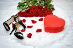 Les boîtes rouges au coeur forment, des chaussures noires et un bouquet des roses rouges sur une fourrure blanche Photo stock