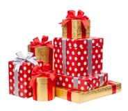 Les boîtes rouges et rayées et d'or avec des cadeaux ont attaché des arcs sur le blanc photographie stock