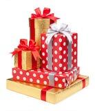 Les boîtes rouges et rayées et d'or avec des cadeaux ont attaché des arcs sur le blanc photos libres de droits