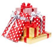 Les boîtes rouges et rayées et d'or avec des cadeaux ont attaché des arcs sur le CCB blanc image stock