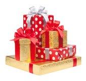 Les boîtes rouges, rayées et d'or avec des cadeaux ont attaché des arcs sur le blanc photographie stock libre de droits