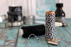 Les bobines avec le ` s de fil et de boulanger tortillent Fils noirs et blancs Photographie stock libre de droits
