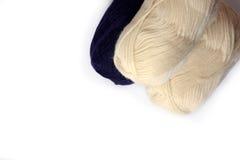 Les bobines blanches et bleu-foncé du tricotage filète sur un fond blanc Photos libres de droits