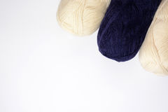 Les bobines blanches et bleu-foncé du tricotage filète sur un fond blanc Photo stock