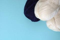 Les bobines blanches et bleu-foncé du tricotage filète sur un fond bleu-clair Image stock