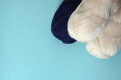 Les bobines blanches et bleu-foncé du tricotage filète sur un fond de turquoise Images stock