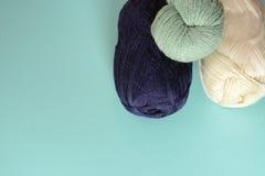 Les bobines blanches, vertes et bleu-foncé du tricotage filète sur un fond de turquoise Photo stock