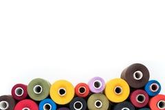 Les bobines colorées de fil d'isolement sur le fond blanc, approvisionnements de couture, textotent la couverture prête, de banni Image libre de droits