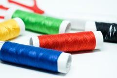 Les bobines du fil coloré se sont concentrées sur la bobine rouge Image stock