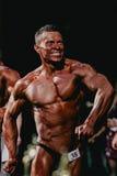 Les bodybuilders de sourire d'athlètes tendent votre coffre et presse photos stock