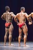 Les Bodybuilders montre à le sien la pose arrière sur l'étape Images stock