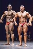 Les Bodybuilders montre sa pose avant sur l'étape Image stock