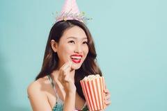 Les boissons asiatiques de femme de mode cokéfient la bouteille au-dessus du fond bleu Images libres de droits
