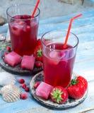 Les boissons de fruit roses fraîches froides ont servi sur la plage sablonneuse avec le coquillage photos libres de droits