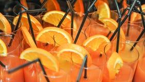 Les boissons fraîches avec les tranches et les pailles oranges, se ferment  Le jus d'orange en verres avec des pailles, préparent Photos stock