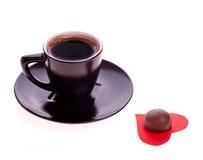 Les bonbons au chocolat au coeur du papier et le café noircissent Photo stock