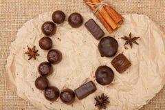 Les bonbons au chocolat rectangulaires et la forme ronde ont mis dessus le papier de paquet Image stock