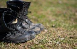 Les bottes d'armée se tiennent dans une rangée sur l'herbe photos stock