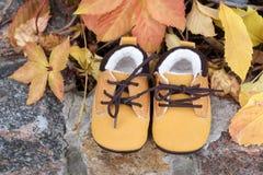 Les bottes de bébé dans la forêt badinent des chaussures avec des feuilles d'automne dehors Image libre de droits
