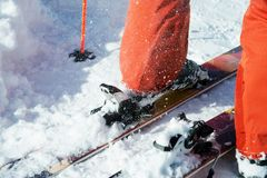 Les bottes de ski alpines oranges dans un ski montent Une botte est complètement fixe sur des skis, le deuxième n'est pas Images stock