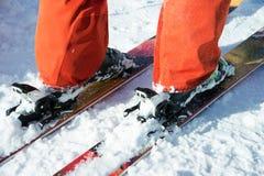 Les bottes de ski alpines oranges dans un ski montent Une botte est complètement fixe sur des skis, le deuxième n'est pas Photos libres de droits