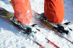 Les bottes de ski alpines oranges dans un ski montent Une botte est complètement fixe sur des skis, le deuxième n'est pas Image libre de droits