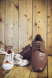 Les bottes du papa et les espadrilles du bébé, Photo stock