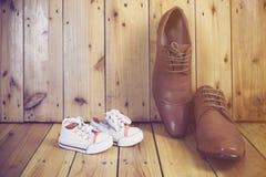 Les bottes du papa et les espadrilles du bébé Photos libres de droits